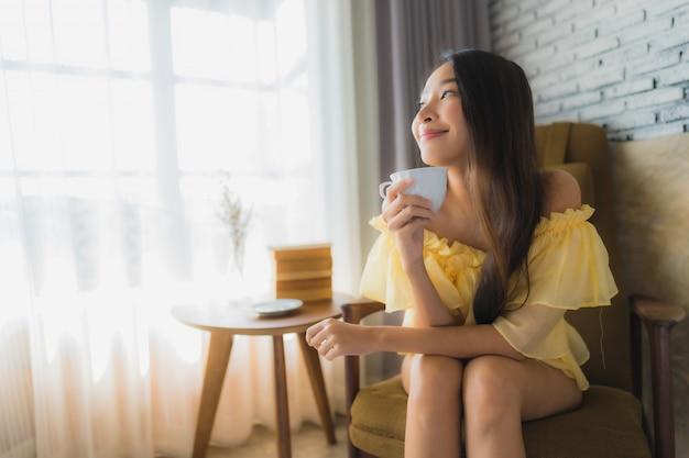 La mujer asiática joven del retrato se sienta en la silla del sofá y lee el libro con la taza de café