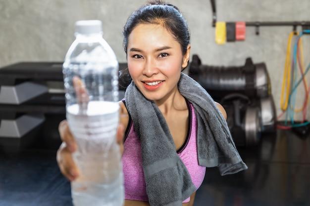 Mujer asiática joven en ropa deportiva agua potable después del ejercicio en el gimnasio.