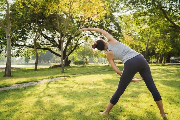 La mujer asiática joven sana del corredor calienta el cuerpo que estira antes de ejercicio y de yoga
