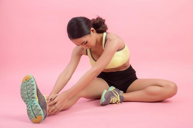 Mujer asiática joven sana hermosa que hace un ejercicio que estira antes de jugar un deporte.