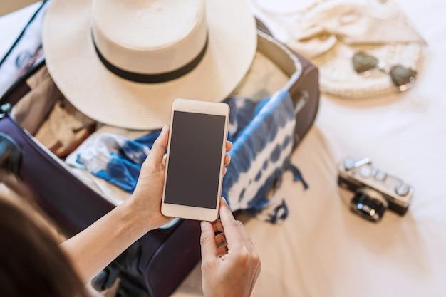Mujer asiática joven sentada en la cama con teléfono inteligente y empacando su maleta preparándose para viajar en vacaciones de verano