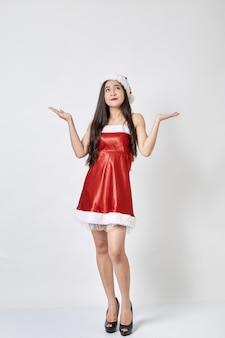 Mujer asiática joven en el sombrero de santa en blanco