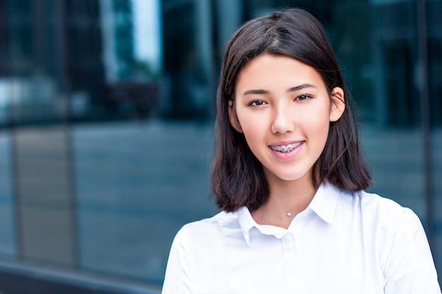 Mujer asiática joven sonriendo y mirando.