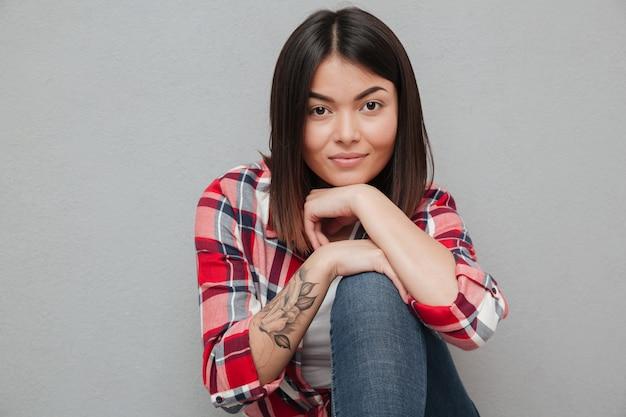 Mujer asiática joven sonriente aislada sobre la pared gris.