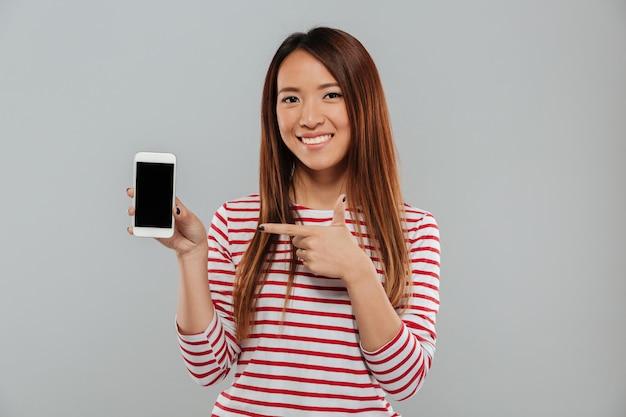 Mujer asiática joven sonriente que muestra la exhibición del teléfono