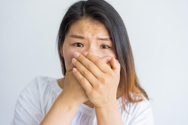 Mujer asiática joven sorprendida nerviosa frustrada con la situación que mira la cámara.