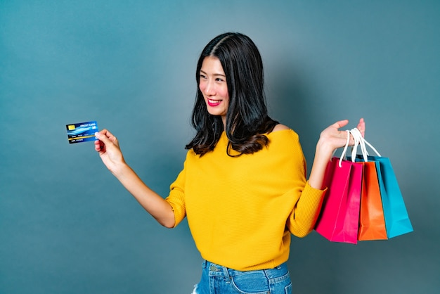 Mujer asiática joven sosteniendo bolsas de la compra y tarjeta de crédito en camisa amarilla en la pared azul
