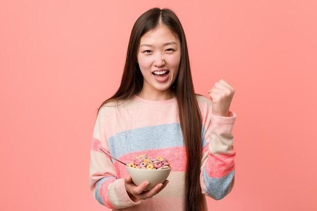 Mujer asiática joven con un tazón de cereal que anima despreocupado y emocionado. concepto de victoria