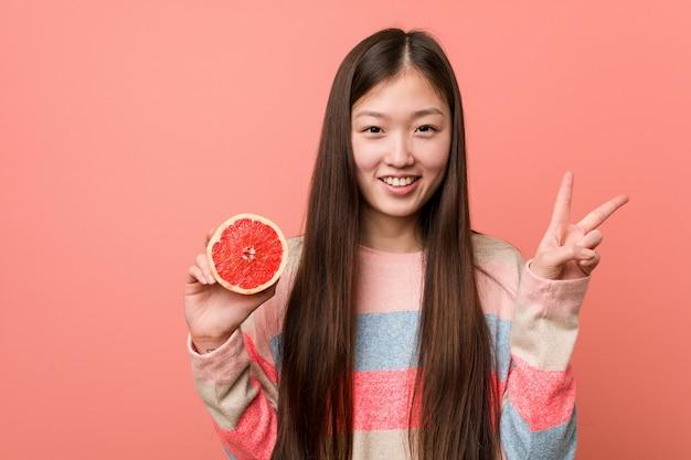 Mujer asiática joven con una toronja que muestra el número dos con los dedos.