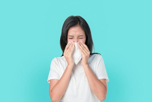 La mujer asiática joven usa una servilleta de papel la boca y la nariz porque la alergia