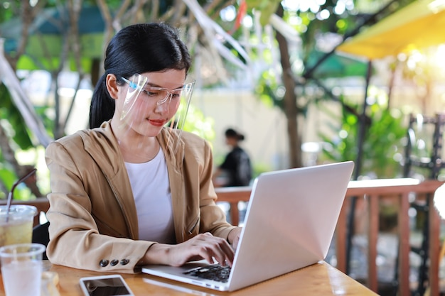 Mujer asiática joven en vestido casual con protector facial y máscara protectora para el cuidado de la salud, sentado en la cafetería y trabajando en computadora portátil y teléfono inteligente. nuevo concepto de distanciamiento normal y social