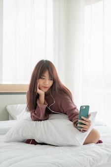 Mujer asiática, juego, smartphone, en cama