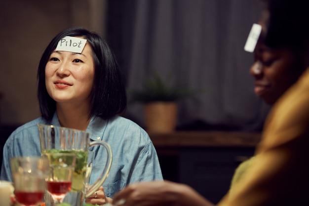 Mujer asiática jugando juego de adivinanzas en la fiesta