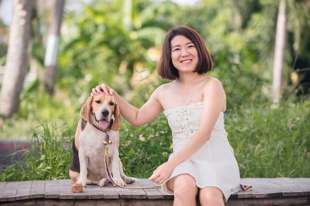 Mujer asiática junto con perro como mejor amigo. estilo de vida al aire libre en solitario en el parque.