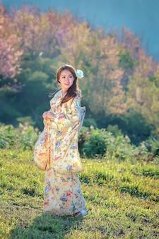 Mujer asiática con kimono tradicional japonés en el jardín de sakura.