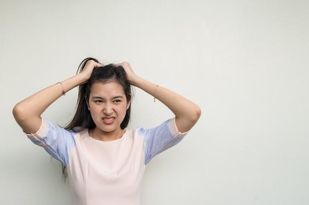 Mujer asiática linda en el fondo blanco de la pared