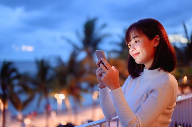 Mujer asiática en línea charlando en el teléfono inteligente en casa. nuevo estilo de vida normal y distanciamiento social.