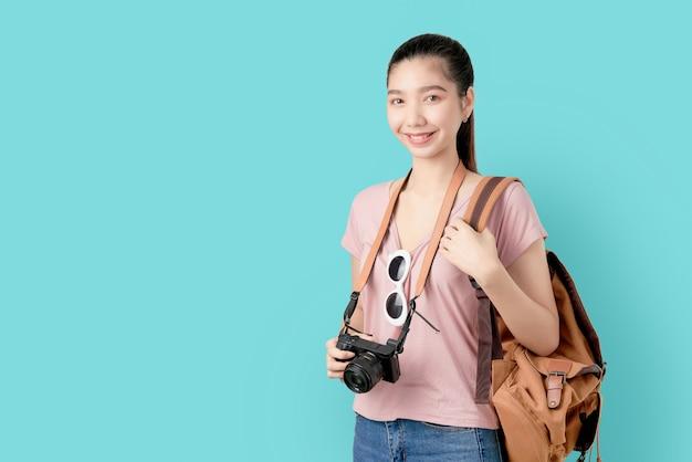 Mujer asiática lista para viajar, turismo y vacaciones con mochila, cámara de fotos.