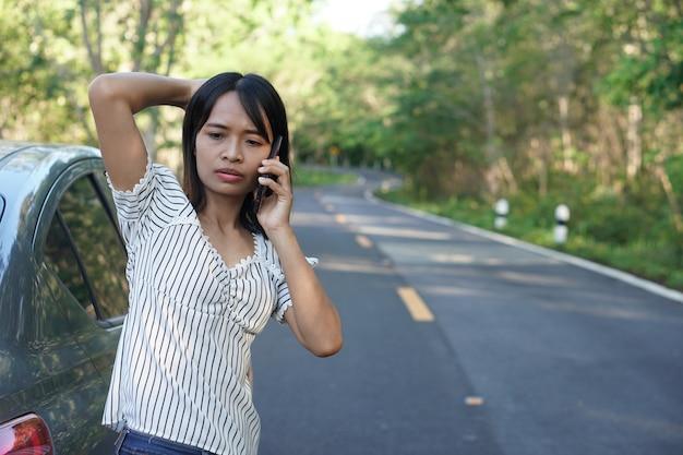 Mujer asiática llama a un mecánico, el auto sale por la carretera alrededor del bosque.
