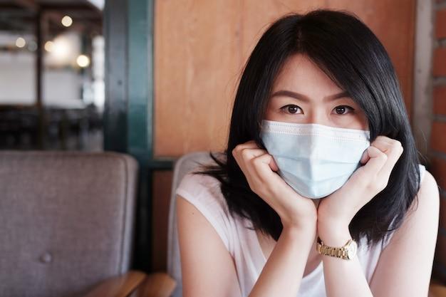 La mujer asiática lleva una máscara para prevenir el covid-19 y la infección por el virus corona o la contaminación del aire pm 2.5. brote de virus en tailandia