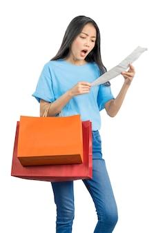Mujer asiática llevando bolsas de la compra sorprendido después de mirar el proyecto de ley aislado sobre fondo blanco.
