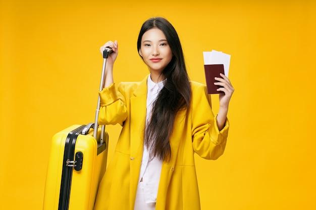 Mujer asiática con una maleta y pasaporte se va de viaje