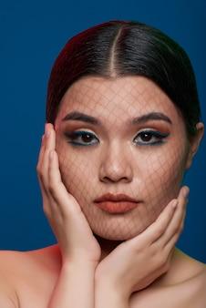 Mujer asiática con maquillaje completo, delgada red que cubre la cara y las manos en las mejillas posando en el estudio