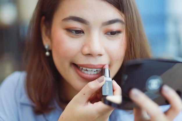 Mujer asiática maquillaje su cara con lápiz labial en café