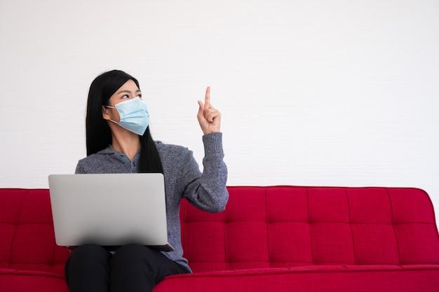 Mujer asiática con una máscara facial y usando una computadora portátil en el sofá para trabajar desde casa