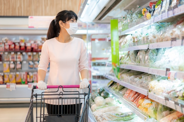 Mujer asiática con máscara higiénica y guante de goma con carrito de compras en el supermercado y buscando un paquete de verduras frescas para comprar durante el brote de covid-19 para prepararse para una cuarentena pandémica