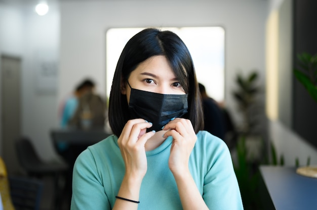 Mujer asiática con máscara médica negra