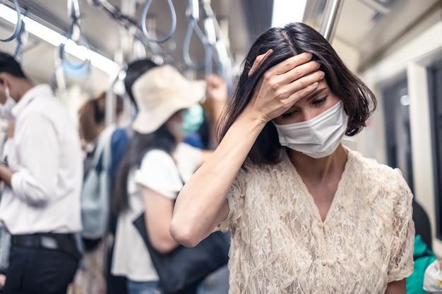 Mujer asiática con máscara para prevenir el anochecer pm 2.5 mala contaminación del aire y coronavirus o covid-19
