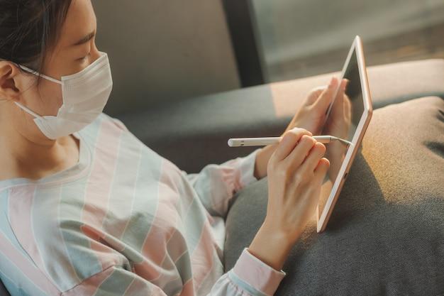 Mujer asiática con máscara protectora de higiene y uso de tableta