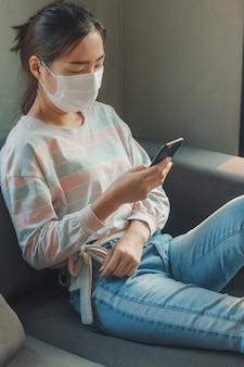 Mujer asiática con máscara protectora de higiene y uso de teléfonos inteligentes