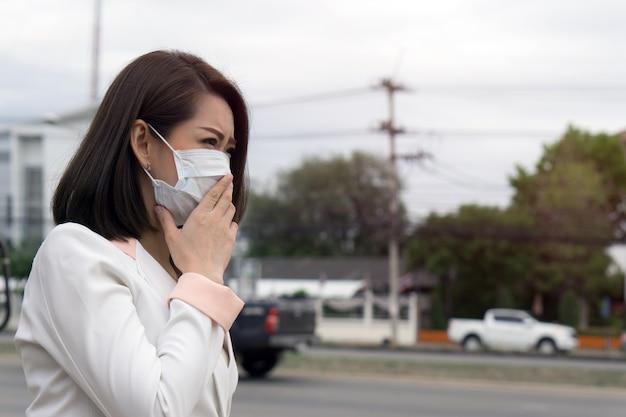 Mujer asiática en máscara protectora sentirse mal en la ciudad con la contaminación del aire.