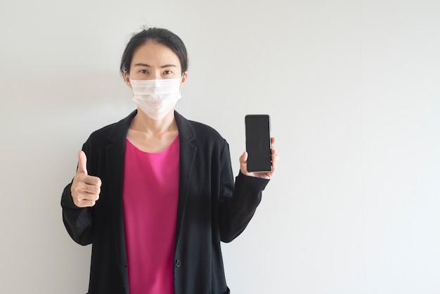 Mujer asiática con máscara quirúrgica muestra teléfono móvil con thrump up para coronavirus, pandemia de virus covid-19, concepto de contaminación del aire