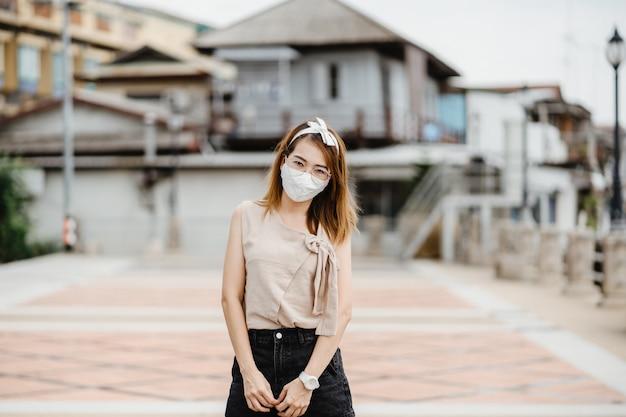 Mujer asiática con mascarilla blanca para proteger el virus de la corona, mascarilla de protección antivirus con estándar para prevenir el coronavirus covid-19