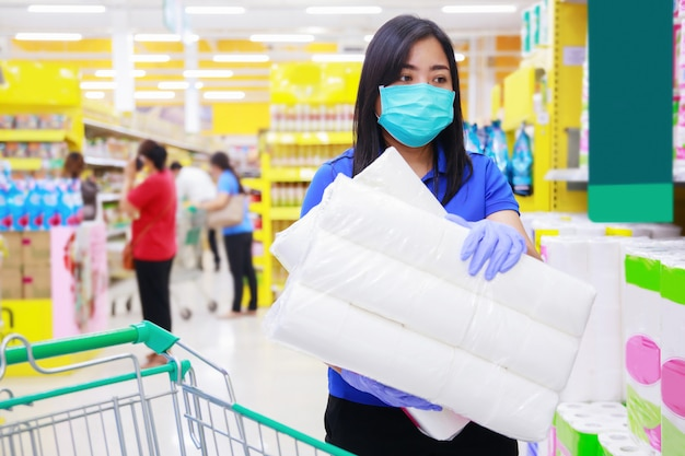Mujer asiática en mascarilla médica y guantes médicos elegir papel higiénico en supermercado