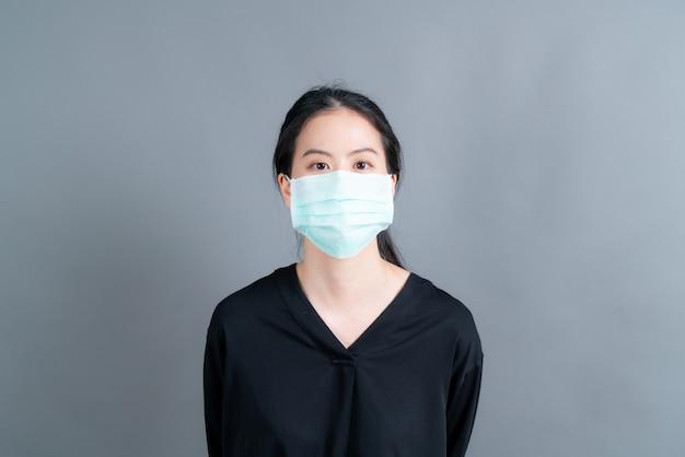 Mujer asiática con mascarilla médica protege el polvo del filtro pm2.5 anti-contaminación, anti-smog y covid-19 sobre fondo gris