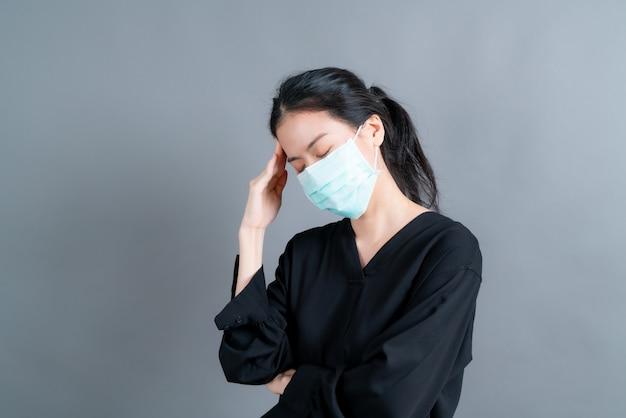Mujer asiática con mascarilla médica que protege el polvo del filtro pm2.5 anti-contaminación, anti-smog y covid-19 y tiene dolor de cabeza