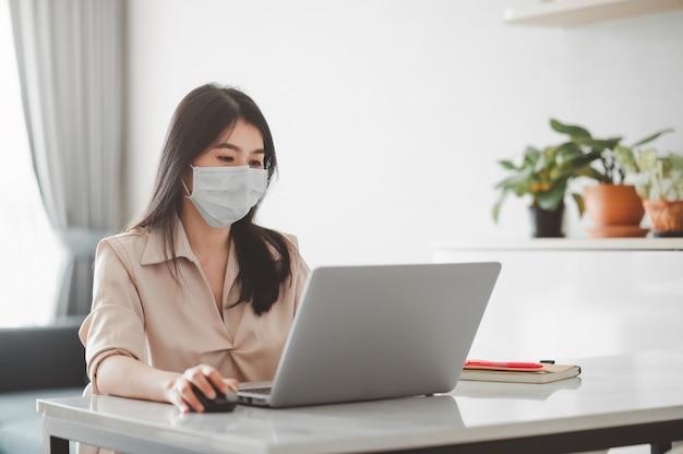 Mujer asiática con mascarilla que trabaja en casa durante la cuarentena por coronavirus usando una computadora portátil