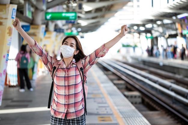 Mujer asiática con mascarilla quirúrgica contra el nuevo coronavirus o enfermedad por coronavirus en la estación de tren pública