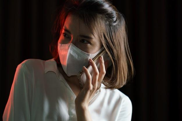 Mujer asiática con mascarilla quirúrgica y hacer una llamada telefónica
