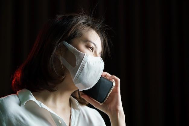 Mujer asiática con mascarilla quirúrgica haciendo una llamada telefónica.