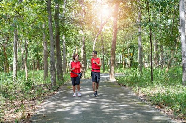 Mujer asiática mayor feliz con el hombre o el entrenador personal que activa ejecutarse en el parque