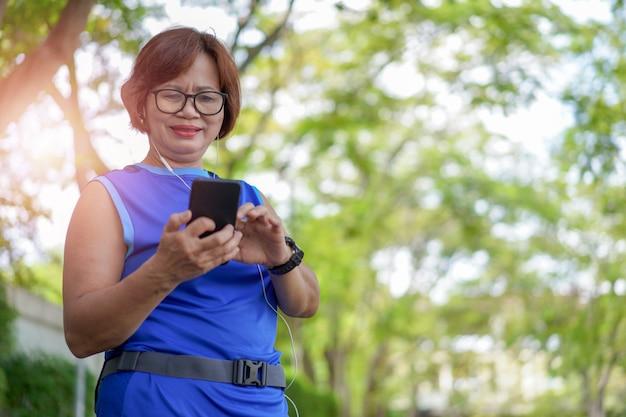 Mujer asiática mayor feliz que sostiene el teléfono elegante con escuchar la música