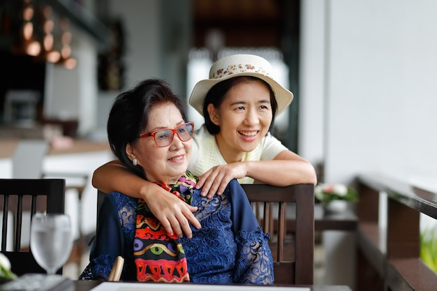 Mujer asiática mayor con hija relajante de vacaciones juntos.
