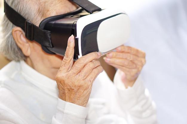Mujer asiática mayor o anciana con gafas de realidad virtual