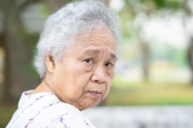 Mujer asiática mayor o anciana sentada en el parque, concepto médico fuerte y saludable.