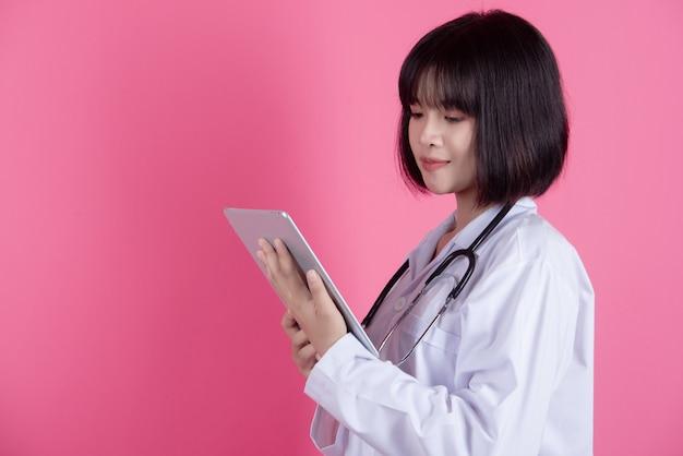 Mujer asiática médico con bata blanca sobre rosa
